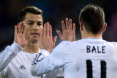 Cristiano Ronaldo of Real Madrid CF clashes hands with his teammate Gareth Bale after a penalty over Bale during the Copa del Rey semifinal second...