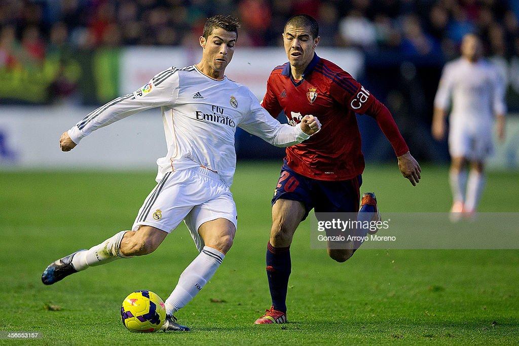 Cristiano Ronaldo (L) of Real Madrid CF competes for the ball with Francisco Andres Silva (R) of CA Osasuna during the La Liga match between CA Osasuna and Real Madrid CF at Estadio El Sadar de Navarra on December 14, 2013 in Pamplona, Spain.