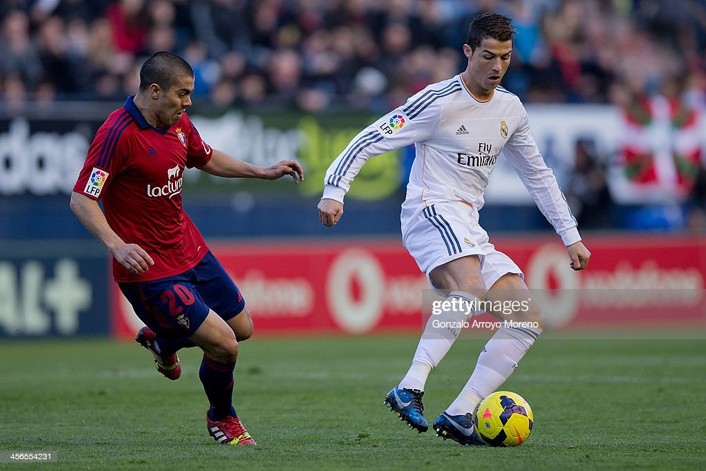 Cristiano Ronaldo (R) of Real Madrid CF competes for the ball with Francisco Andres Silva (L) of CA Osasuna during the La Liga match between CA Osasuna and Real Madrid CF at Estadio El Sadar de Navarra on December 14, 2013 in Pamplona, Spain.