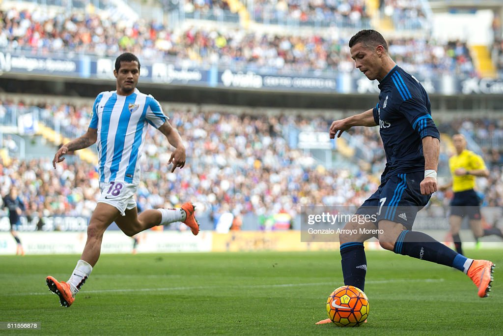 Cristiano Ronaldo of Real Madrid CF competes for the ball with Roberto Rosales of Malaga CF during the La Liga match between Malaga CF and Real...