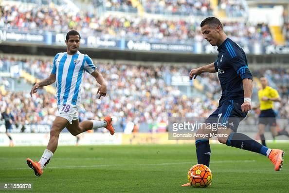Cristiano Ronaldo of Real Madrid CF competes for the ball with Roberto Rosales of Malaga CF during the La Liga match between Malaga CF and Real...