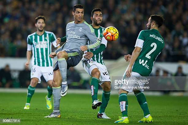 Cristiano Ronaldo of Real Madrid CF competes for the ball with Petros Matheus of Real Betis Balompie and his teammate Francisco Jose Molinero during...
