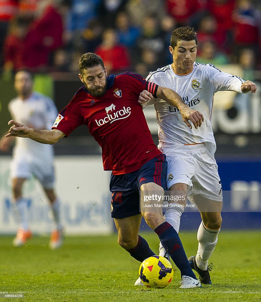 Cristiano Ronaldo of Real Madrid CF duels for the ball with Damia Abella of CA Osasuna during the La Liga match between CA Osasuna and Real Madrid CF at Estadio Reyno de Navarra on December 14, 2013 in Pamplona, Spain.