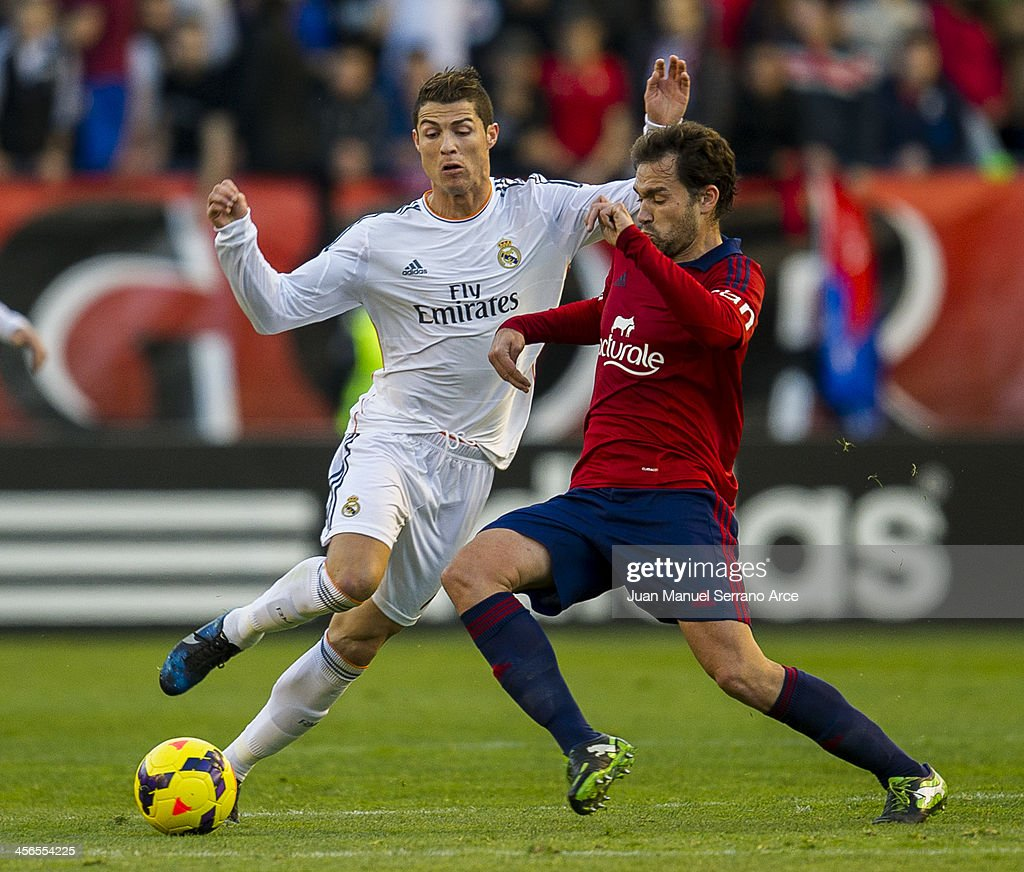 Cristiano Ronaldo of Real Madrid CF duels for the ball with Manuel Jesus Ortiz 'Lolo' of CA Osasuna during the La Liga match between CA Osasuna and Real Madrid CF at Estadio Reyno de Navarra on December 14, 2013 in Pamplona, Spain.