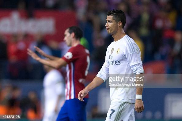Cristiano Ronaldo of Real Madrid CF gestures as he leaves the pithc ahead Diego Godin of Atletico de Madrid after the La Liga match between Club...