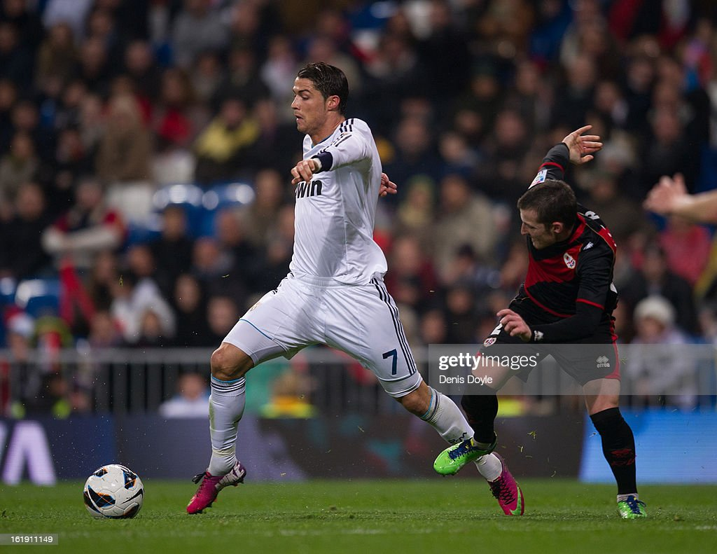 <a gi-track='captionPersonalityLinkClicked' href=/galleries/search?phrase=Cristiano+Ronaldo+-+Soccer+Player&family=editorial&specificpeople=162689 ng-click='$event.stopPropagation()'>Cristiano Ronaldo</a> (L) of Real Madrid CF gets past Roberto Roman 'Tito' of Rayo Vallecano during the La Liga match between Real Madrid CF and Rayo Vallecano at estadio Santiago Bernabeu on February 17, 2013 in Madrid, Spain.