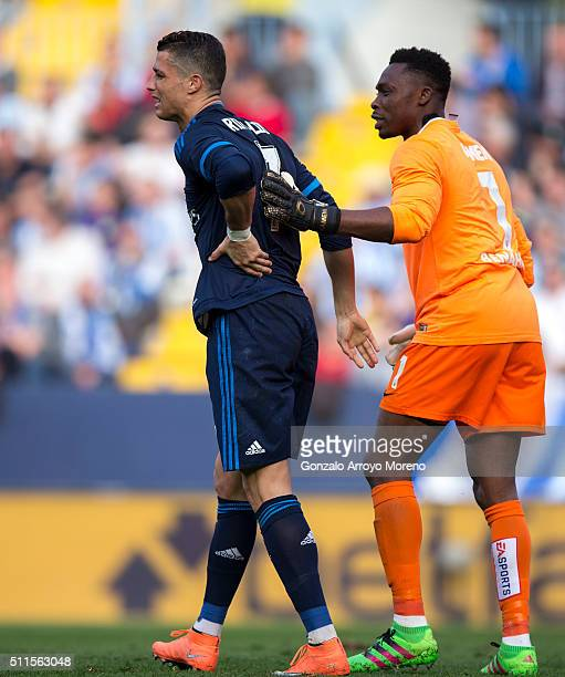 Cristiano Ronaldo of Real Madrid CF grimmaces in pain as Idriss Carlos Kameni of Malaga CF helps him during the La Liga match between Malaga CF and...