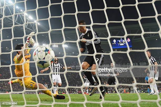 Cristiano Ronaldo of Real Madrid CF heads the ball past goalkeeper Gianluigi Buffon of Juventus to score their first and equalising goal during the...