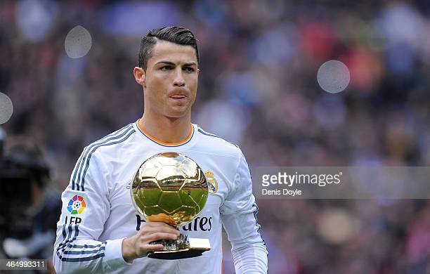Cristiano Ronaldo of Real Madrid CF holds the Ballon d'Or 2013 award prior to he start of the La Liga match between Real Madrid CF and Granada CF at...