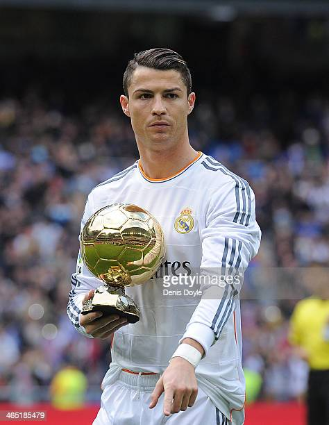 Cristiano Ronaldo of Real Madrid CF holds the Ballon d'Or 2013 award prior to the start of the La Liga match between Real Madrid CF and Granada CF at...