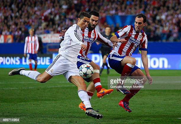 Cristiano Ronaldo of Real Madrid CF is closed down by Arda Turan and Diego Godín of Atletico Madrid during the UEFA Champions League Quarter Final...