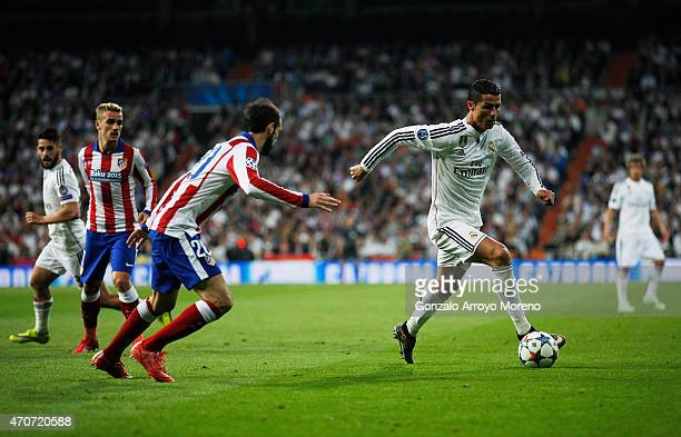 Cristiano Ronaldo of Real Madrid CF is watched by Juanfran of Atletico Madrid during the UEFA Champions League quarterfinal second leg match between...