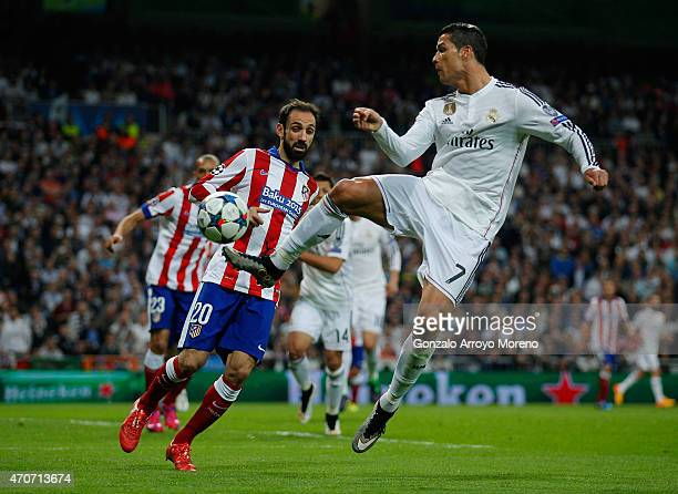 Cristiano Ronaldo of Real Madrid CF jumps for the ball ahead of Juanfran of Atletico Madrid during the UEFA Champions League quarterfinal second leg...