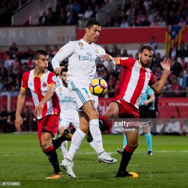 Cristiano Ronaldo of Real Madrid CF kicks the ball under pressure from Christian Stuani of Girona FC during the La Liga match between Girona and Real...