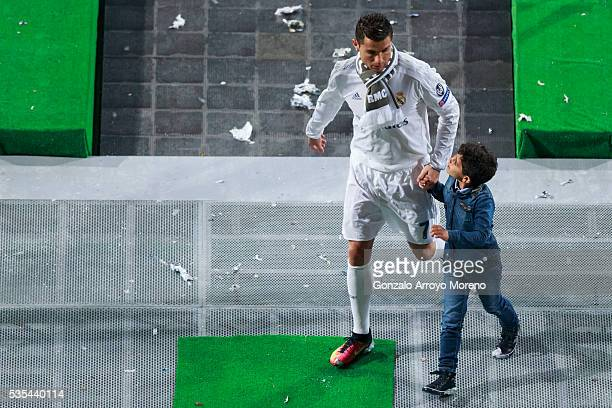 Cristiano Ronaldo of Real Madrid CF leaves the pitch with his son Cristiano Ronaldo Jr after the celebration with their fans at Santiago Bernabeu...