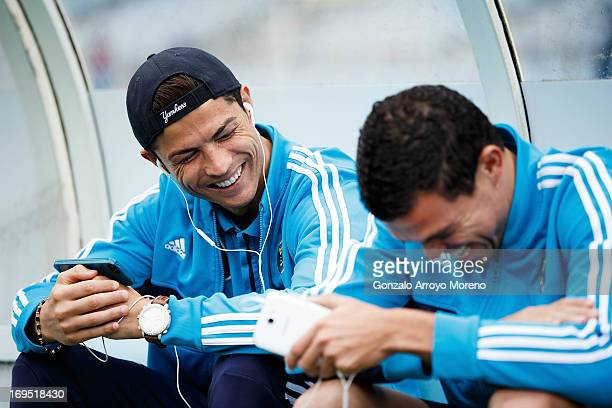 Cristiano Ronaldo of Real Madrid CF listens to music with teammate Pepe on their cell phones prior to start the La Liga match between Real Sociedad...