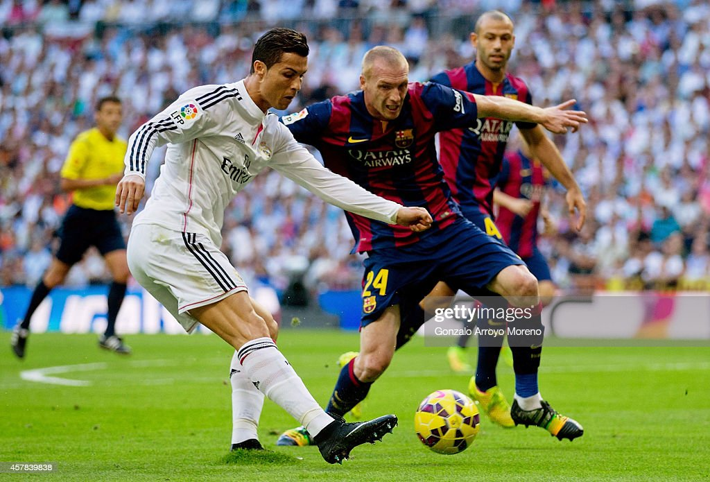 Cristiano Ronaldo of Real Madrid CF looks to cross the ball under pressure from Jeremy Mathieu of Barcelona during the La Liga match between Real Madrid CF and FC Barcelona at Estadio Santiago Bernabeu on October 25, 2014 in Madrid, Spain.