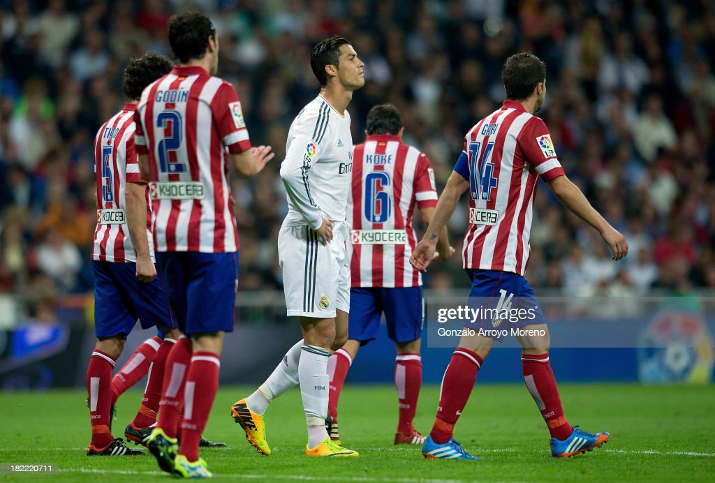 Cristiano Ronaldo of Real Madrid CF reacts after failing to score surrounded by Atletico de Madrid players during the La Liga match between Real Madrid CF and Club Atletico de Madrid at Estadio Santiago Bernabeu on September 28, 2013 in Madrid, Spain.