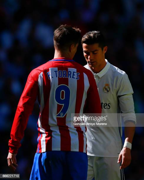 Cristiano Ronaldo of Real Madrid CF reacts as Fernando Torres of Atletico de Madrid speaks to him during the La Liga match between Real Madrid CF and...