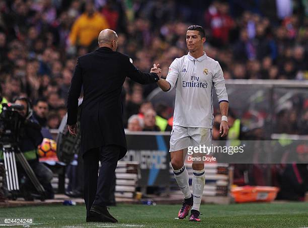 Cristiano Ronaldo of Real Madrid CF shakes hands with Real manager Zinedine Zidane on being substituted in the La Liga match between Club Atletico de...