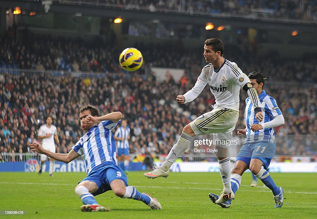 Cristiano Ronaldo (R) of Real Madrid CF shoots past Mikel Gonzalez (L) of Real Sociedad de Futbol during the La Liga match between Real Madrid CF and Real Sociedad de Futbol at estadio Santiago Bernabeu on January 6, 2013 in Madrid, Spain.