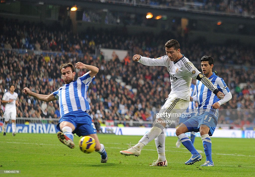 Cristiano Ronaldo (R) of Real Madrid CF shoots past Mikel Gonzalez of Real Sociedad de Futbol during the La Liga match between Real Madrid CF and Real Sociedad de Futbol at estadio Santiago Bernabeu on January 6, 2013 in Madrid, Spain.