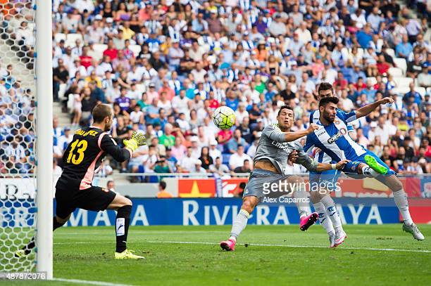 Cristiano Ronaldo of Real Madrid CF shoots towards goal with the opposition of Ruben Duarte of RCD Espanyol and scores his team's third goal during...