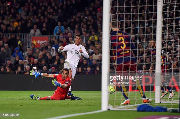 Cristiano Ronaldo of Real Madrid CF slides the ball underneat6h Claudio Bravo of FC Barcelona to score his team's second goal during the La Liga...