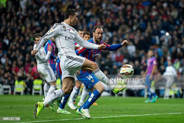 Cristiano Ronaldo of Real Madrid CF strikes the ball ahead Ivan Ramis of Levante UD during the La Liga match between Real Madrid CF and Levante UD at...
