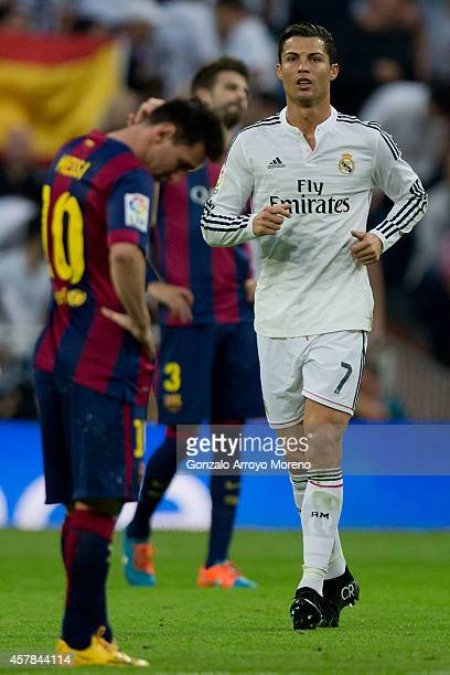 Cristiano Ronaldo of Real Madrid CF walks on after celebrating his team's third goal close to Lionel Messi of FC Barcelonar reacting defeated during...