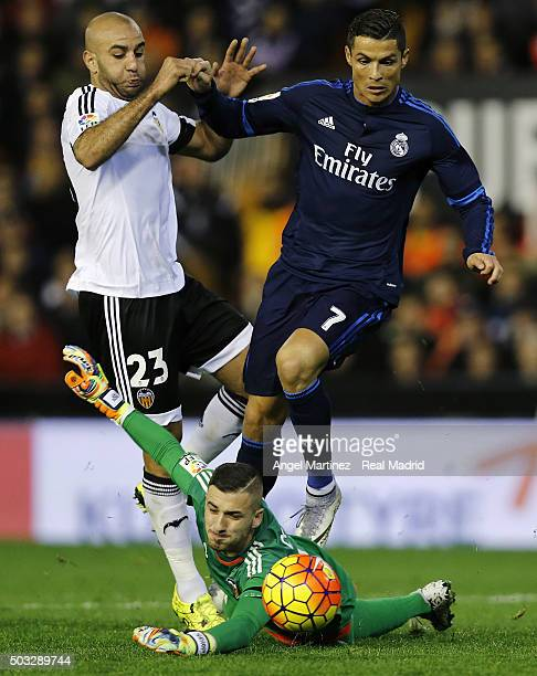 Cristiano Ronaldo of Real Madrid competes for the ball with Aymen Abdennour and Jaume Domenech of Valencia CF during the La Liga match between...
