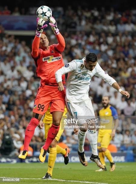 Cristiano Ronaldo of Real Madrid competes for the ball with Boy Waterman of APOEL Nikosia during the UEFA Champions League group H match between Real...