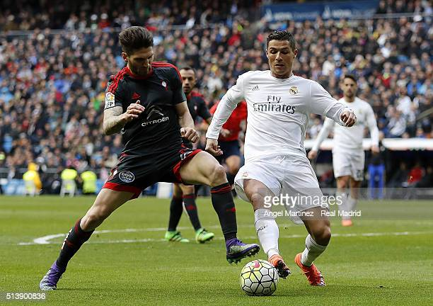 Cristiano Ronaldo of Real Madrid competes for the ball with Carles Planas of Celta Vigo during the La Liga match between Real Madrid CF and Celta...