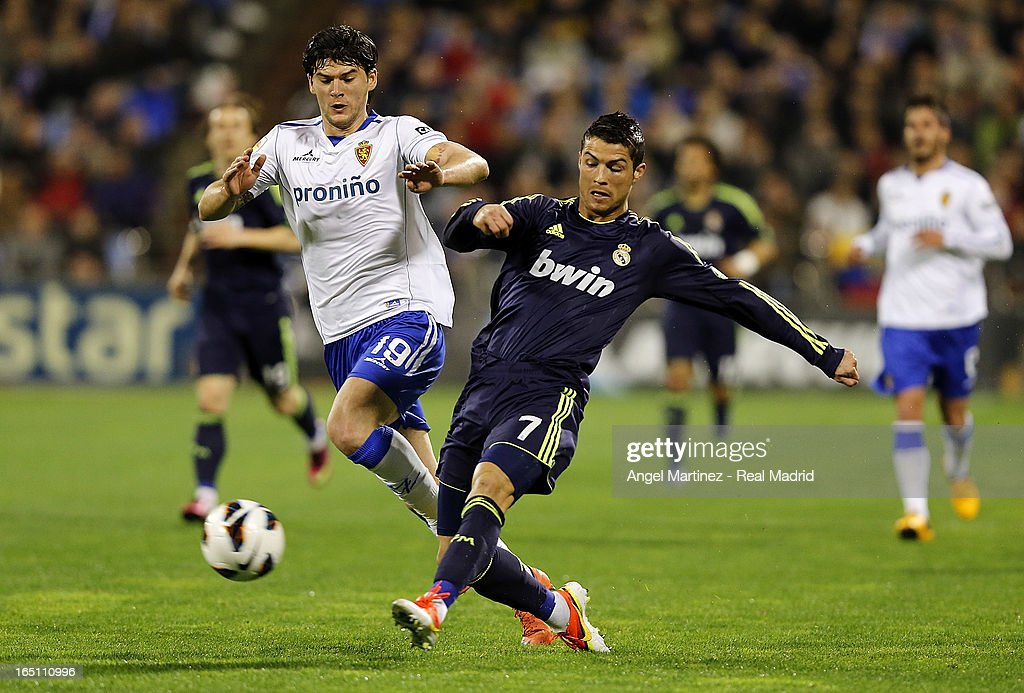 <a gi-track='captionPersonalityLinkClicked' href=/galleries/search?phrase=Cristiano+Ronaldo+-+Soccer+Player&family=editorial&specificpeople=162689 ng-click='$event.stopPropagation()'>Cristiano Ronaldo</a> of Real Madrid competes for the ball with <a gi-track='captionPersonalityLinkClicked' href=/galleries/search?phrase=Cristian+Sapunaru&family=editorial&specificpeople=633831 ng-click='$event.stopPropagation()'>Cristian Sapunaru</a> of Real Zaragoza during the La Liga match between Real Zaragoza and Real Madrid at La Romareda on March 30, 2013 in Zaragoza, Spain.