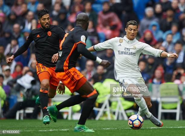 Cristiano Ronaldo of Real Madrid competes for the ball with Ezequiel Garay and Eliaquim Mangala of Valencia during the La Liga match between Real...