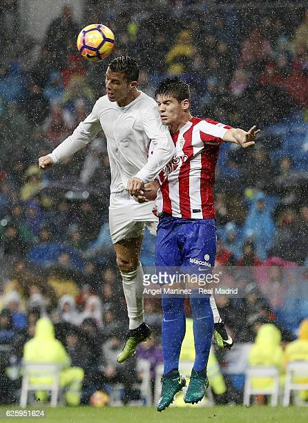 Cristiano Ronaldo of Real Madrid competes for the ball with Jorge Mere of Real Sporting de Gijon during the La Liga match between Real Madrid CF and...