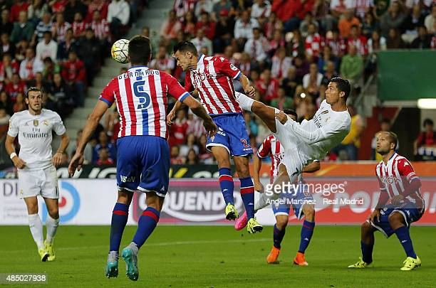Cristiano Ronaldo of Real Madrid competes for the ball with Luis Hernandez of Sporting Gijon during the La Liga match between Sporting Gijon and Real...