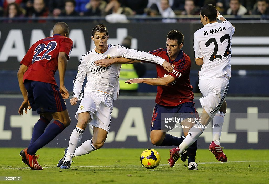 <a gi-track='captionPersonalityLinkClicked' href=/galleries/search?phrase=Cristiano+Ronaldo+-+Soccer+Player&family=editorial&specificpeople=162689 ng-click='$event.stopPropagation()'>Cristiano Ronaldo</a> of Real Madrid competes for the ball with Marc Bertran of CA Osasuna during the La Liga match between CA Osasuna and Real Madrid at Estadio Reyno de Navarra on December 14, 2013 in Pamplona, Spain.