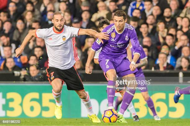 Cristiano Ronaldo of Real Madrid competes for the ball with Mario Suarez Mata of Valencia CF during their La Liga match between Valencia CF and Real...