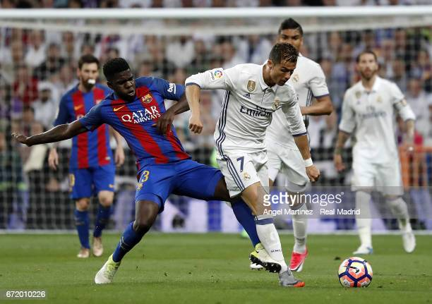 Cristiano Ronaldo of Real Madrid competes for the ball with Samuel Umtiti of FC Barcelona during the La Liga match between Real Madrid and FC...