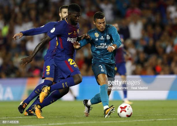 Cristiano Ronaldo of Real Madrid competes for the ball with Samuel Umtiti of FC Barcelona during the Supercopa de Espana Final first leg match...