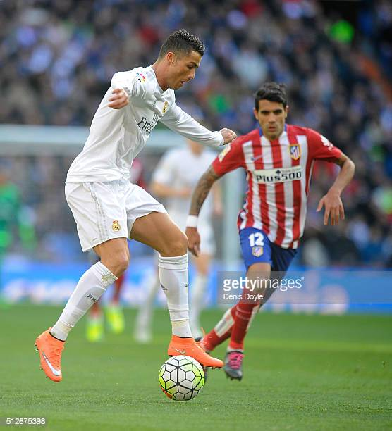 Cristiano Ronaldo of Real Madrid controls the ball beside Augusto Fernandez of Club Atletico de Madrid during the La Liga match between Real Madrid...