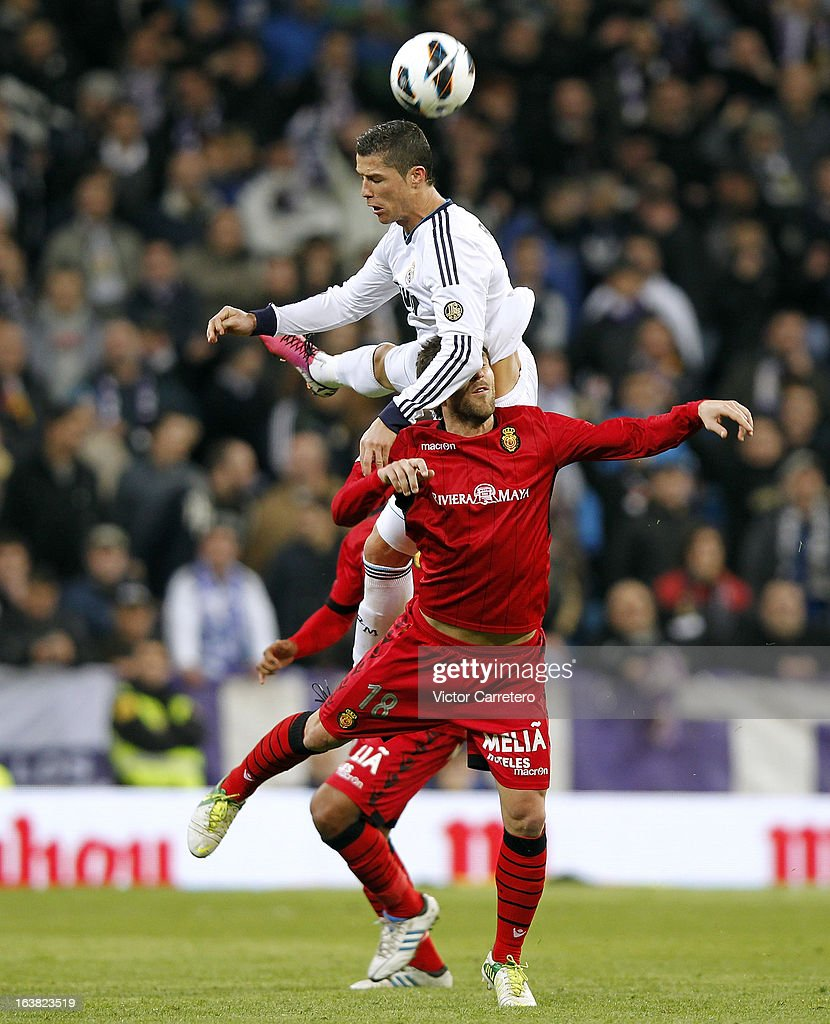 <a gi-track='captionPersonalityLinkClicked' href=/galleries/search?phrase=Cristiano+Ronaldo+-+Soccer+Player&family=editorial&specificpeople=162689 ng-click='$event.stopPropagation()'>Cristiano Ronaldo</a> (TOP) of Real Madrid duels for the ball with Victor Casadesus of Mallorca during the La Liga match between Real Madrid and RCD Mallorca at Estadio Santiago Bernabeu on March 16, 2013 in Madrid, Spain.