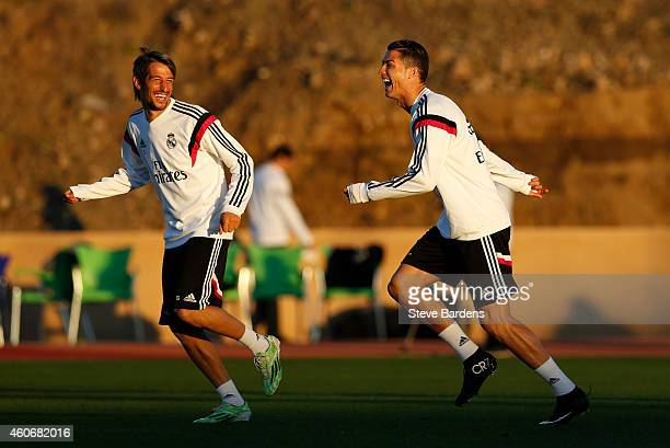 Cristiano Ronaldo of Real Madrid enjoys a joke with Fabio Coentrao during a training session at Le Grande Stade de Marrakech on December 19 2014 in...