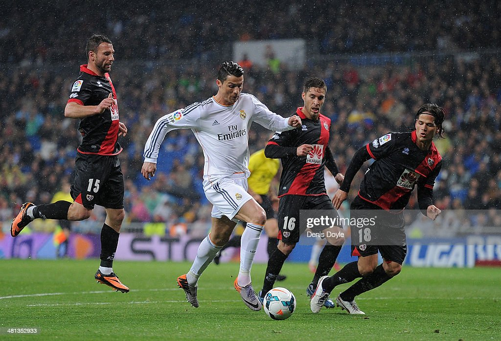 <a gi-track='captionPersonalityLinkClicked' href=/galleries/search?phrase=Cristiano+Ronaldo+-+Calciatore&family=editorial&specificpeople=162689 ng-click='$event.stopPropagation()'>Cristiano Ronaldo</a> (C) of Real Madrid FC runs past <a gi-track='captionPersonalityLinkClicked' href=/galleries/search?phrase=Razvan+Rat&family=editorial&specificpeople=2147212 ng-click='$event.stopPropagation()'>Razvan Rat</a> (#15), Ruben Rochina (#16) and Ze Castro of Rayo Vallecano de Madrid during the La Liga match between Real Madrid CF and Rayo Vallecano de Madrid at Santiago Bernabeu stadium on March 29, 2014 in Madrid, Spain.