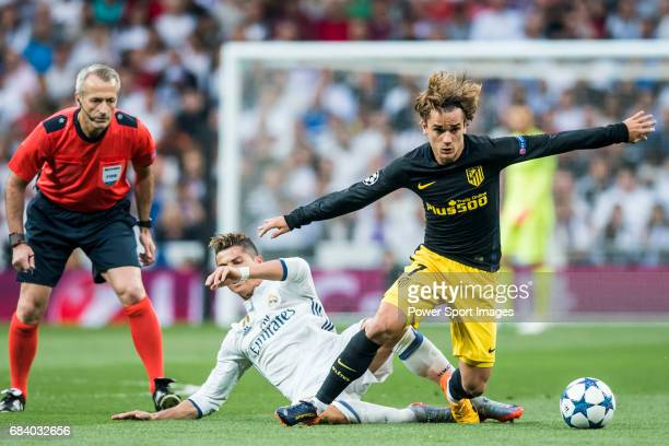 Cristiano Ronaldo of Real Madrid fights for the ball with Antoine Griezmann of Atletico de Madrid with referee 'nMartin Atkinson watching on during...