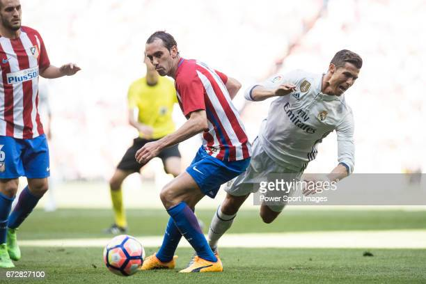 Cristiano Ronaldo of Real Madrid fights for the ball with Diego Roberto Godin Leal of Atletico de Madrid during their La Liga match between Real...