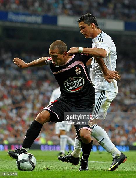 Cristiano Ronaldo of Real Madrid fights for the ball with Juliano Antonello of Deportivo la Coruna during the La Liga match between Real Madrid and...