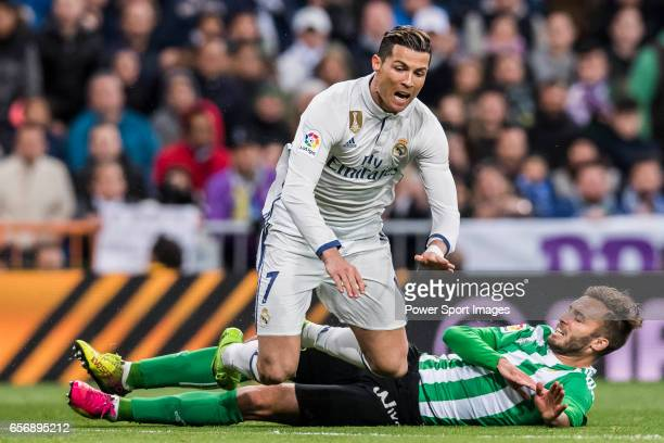 Cristiano Ronaldo of Real Madrid gets tripped while battling for the ball with German Pezzella of Real Betis during their La Liga match between Real...
