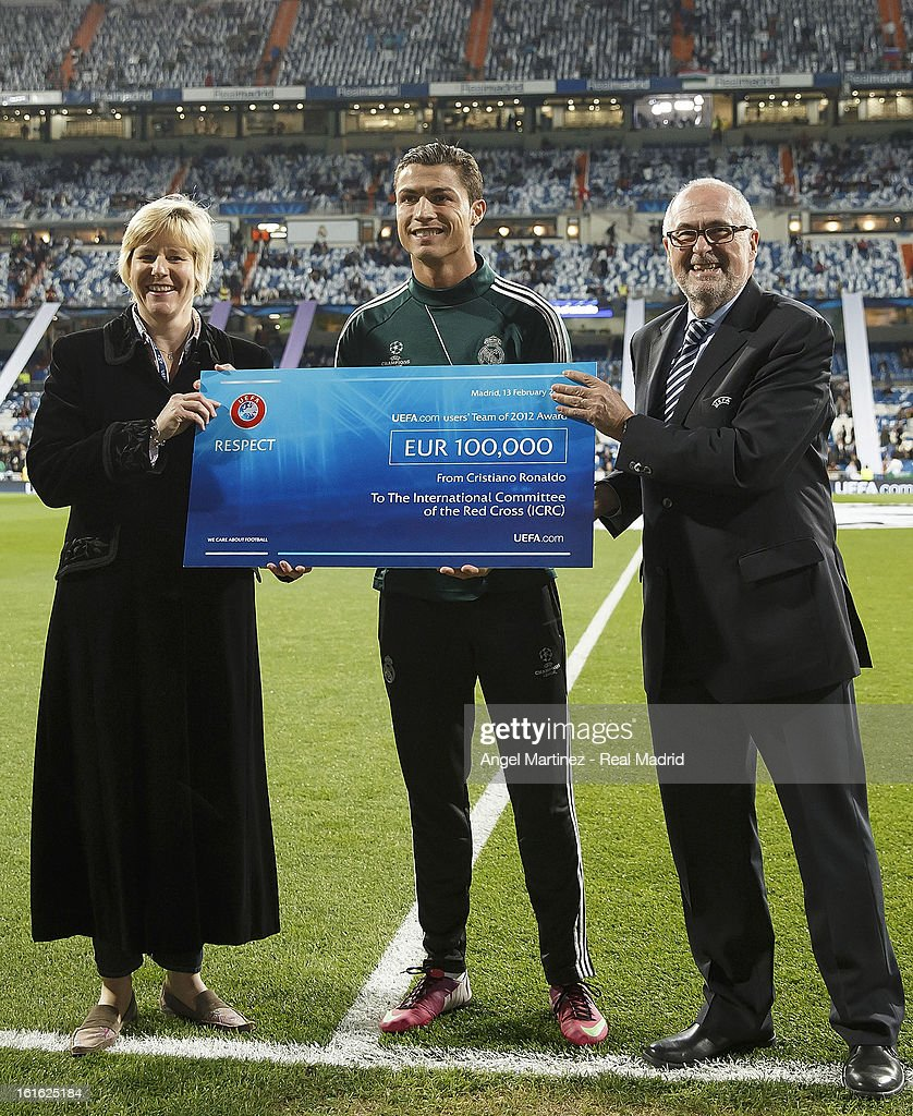 Cristiano Ronaldo (C) of Real Madrid gives a cheque from UEFA to Caroline Welch-Ballentine (L) of International Committee of the Red Cross to support the rehabilitation of land-mine victims in Afghanistan before the UEFA Champions League Round of 16 first leg match between Real Madrid and Manchester United at Estadio Santiago Bernabeu on February 13, 2013 in Madrid, Spain.